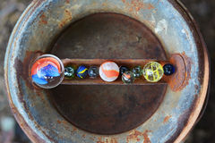 Have you lost your marbles. Row of colorful glass marbles on vintage rusty metal milk can Stock Images