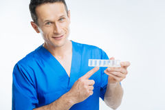 Mature practitioner posing with pills organizer Royalty Free Stock Image