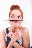 Have young red-haired woman makes fun with a paintbrush Stock Image