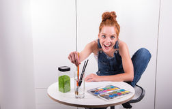 Have young red-haired woman paints picture in her spare time Royalty Free Stock Image