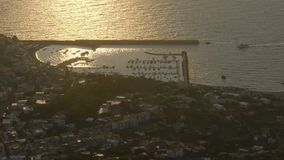 Haven door kuststad met boten van overzees door golfbreker in zonsonderganggloed die worden gescheiden stock videobeelden
