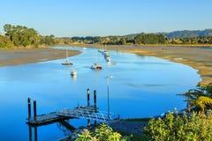 Haven at low tide, met boten in een kanaal tussen de zandvlakten stock fotografie