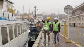 Havenarbeiders in helmen die dichtbij de boot spreken