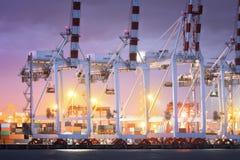 Havenkranen die in zeehaven, Kraan werken van vrachtdok, Werkende kraanbrug in scheepswerf bij schemering stock foto's