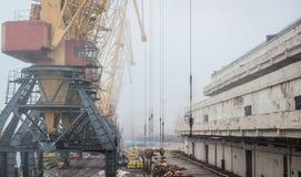 Havenpakhuis met helling en kranen en andere infrastructuur stock afbeeldingen