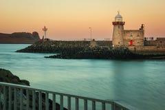 Havenvuurtoren bij zonsondergang Howth ierland Stock Afbeelding