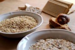 Haver en rijst in een kom Rijstcakes en brood op achtergrond Voedsel hoog in koolhydraat Stock Afbeelding