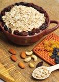Havermeel in ceramische plaat, lepel, rozijnen, cachou en amandelen Stock Foto