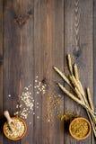 Havermeel en haver in kommen dichtbij twijgen van tarwe op de donkere houten ruimte van het achtergrond hoogste meningsexemplaar Royalty-vrije Stock Afbeeldingen