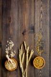 Havermeel en haver in kommen dichtbij twijgen van tarwe op de donkere houten ruimte van het achtergrond hoogste meningsexemplaar Stock Fotografie