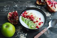Havermeel en yoghurt smoothie kom met kiwiplakken en pomegrana stock fotografie