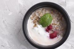 Havermeel met frambozen en gestremde melk in de container van het ecovoedsel stock afbeeldingen