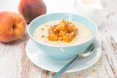 Havermeel met gekarameliseerde perziken in een kom en een yoghurt Stock Foto's