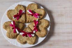 Havermeelkoekjes in de vorm van hart met brief en lint Stock Foto