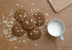 Havermeelkoekjes en een mok melk op een bruine achtergrond Royalty-vrije Stock Foto's