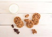 Havermeelkoekjes met chocolade en een glas melk op houten bac royalty-vrije stock fotografie
