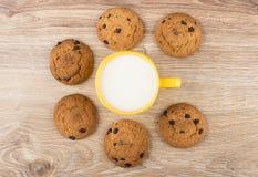Havermeelkoekjes met chocolade rond kop van melk op lijst stock afbeeldingen