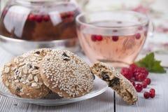 Havermeelkoekjes met sesam en thee in een kop en een theepot Royalty-vrije Stock Fotografie