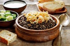 Havermoutpap met wilde rijst en zwarte linzen met gebraden uien wordt gemaakt die Stock Foto's