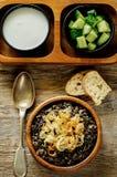 Havermoutpap met wilde rijst en zwarte linzen met gebraden uien wordt gemaakt die Royalty-vrije Stock Afbeelding