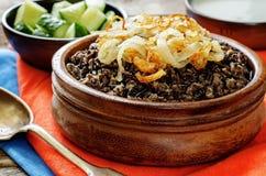 Havermoutpap met wilde rijst en zwarte linzen met gebraden uien wordt gemaakt die Royalty-vrije Stock Fotografie