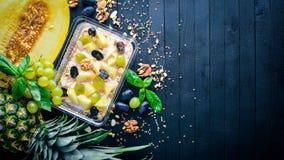 Havermoutpap met yoghurt, ananas, druiven, en meloenen Gezond dieetvoedsel Lunch het In dozen doen Stock Fotografie