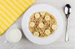 Havermoutpap van havervlokken met banaan, melk in kop, servet Royalty-vrije Stock Foto