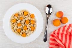 Havermoutpap van havervlokken met stukken abrikozen, lepel, servet Royalty-vrije Stock Foto