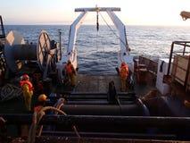 Havet av Okhotsk/Ryssland - Juli 17 2015: Vetenskapsexpeditionlag på aktern av RV Akademik Lavrentyev som hissar utrustning upp w arkivfoto