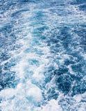 Havet för skeppvakvågen spårar på blå bakgrund för havsvatten arkivfoto