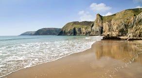 Havet möter sand som reflekterar den imponerande Pembroke Coastline mellan Lydstep och den Manorbier fjärden royaltyfri fotografi