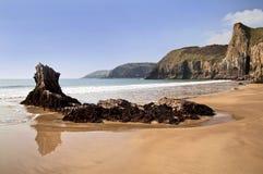 Havet möter sand som reflekterar under Pembroke Coastline mellan Lydstep och den Manorbier fjärden arkivfoto