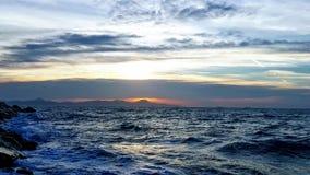 Havet ser ilsken himmel med solnedgång bakom royaltyfri bild