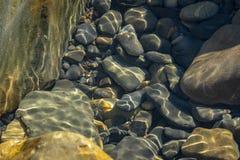 Havet stenar och vaggar av olik format och texsture av svart, grått och brunt under vattnet på Blacket Sea arkivbild