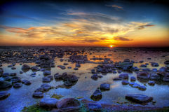 havet stenar solnedgång Arkivbild