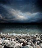Havet stenar vågor och mörk himmel Fotografering för Bildbyråer