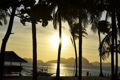 Havet stranden, vågor, gömma i handflatan upplyst solljus för dunge till och med molnen på solnedgången Filippinerna för El Nido  arkivbilder