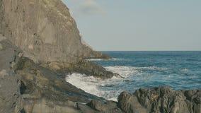 Havet vågor för blått vatten som kraschar på vulkaniskt, vaggar arkivfilmer