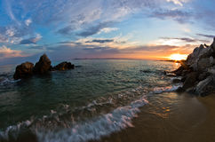Havet vaggar på en sandig strand på solnedgången i Sithonia, Chalkidiki Arkivfoto