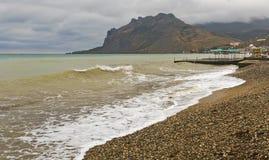 Havet vinkar att svepa på en öde strand i dåligt väder royaltyfri fotografi