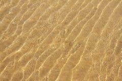 Havet vinkar i en sandig strand Arkivfoto