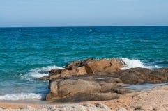 Havet vinkar nära klippan Vitt skum av en havsvåg Djupt mörker - blåa havsvågor som bryter på a, vaggar på den Lloret de mars str Royaltyfri Foto