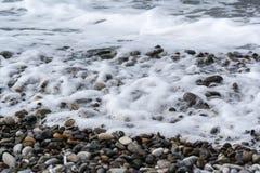 Havet vinkar på en pebbly kust Royaltyfria Bilder