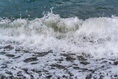 Havet vinkar på en pebbly kust Arkivfoto
