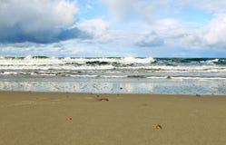 Havet vinkar tvätta den sandiga kusten Arkivfoto