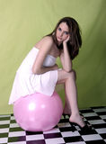 Having a ball. Pretty young model sitting on large pink ball Stock Photography