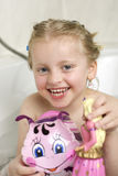 Having a bath. Child sitting in a bath tube and plays Stock Image
