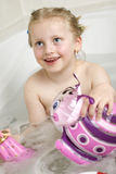 Having a bath. Child sitting in a bath tube and plays Royalty Free Stock Image