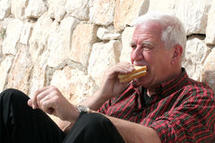 Having a break. Senior sitting next to a wall eating a sandwich Royalty Free Stock Photos