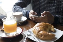 Having breakfast with the cellphone Royalty Free Stock Photography